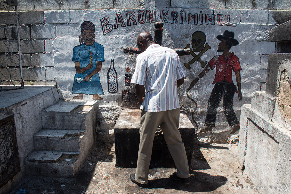 Real Haitian vodou: My guide, Sidney, makes an offering to Baron Kriminel at a fire-stained altar.