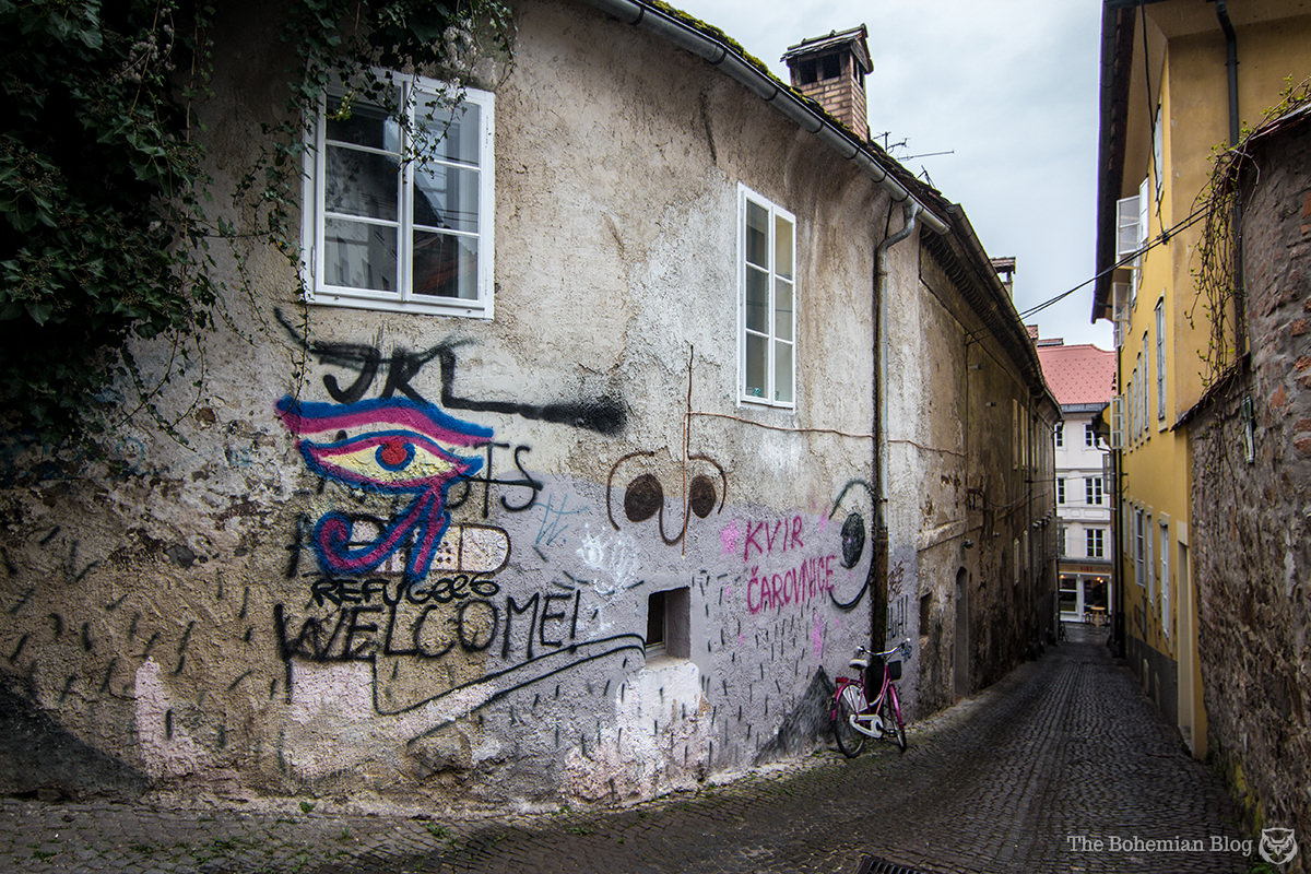 A graffitied slogan in Ljubljana reads 'Refugees Welcome!'... over an older piece, reading 'Islamists Not Welcome.'