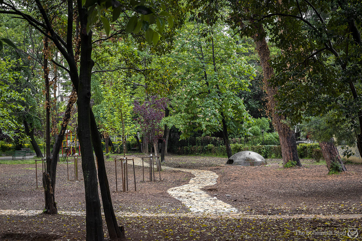 A lonely bunker emerges from the surface of a park in central Tirana.