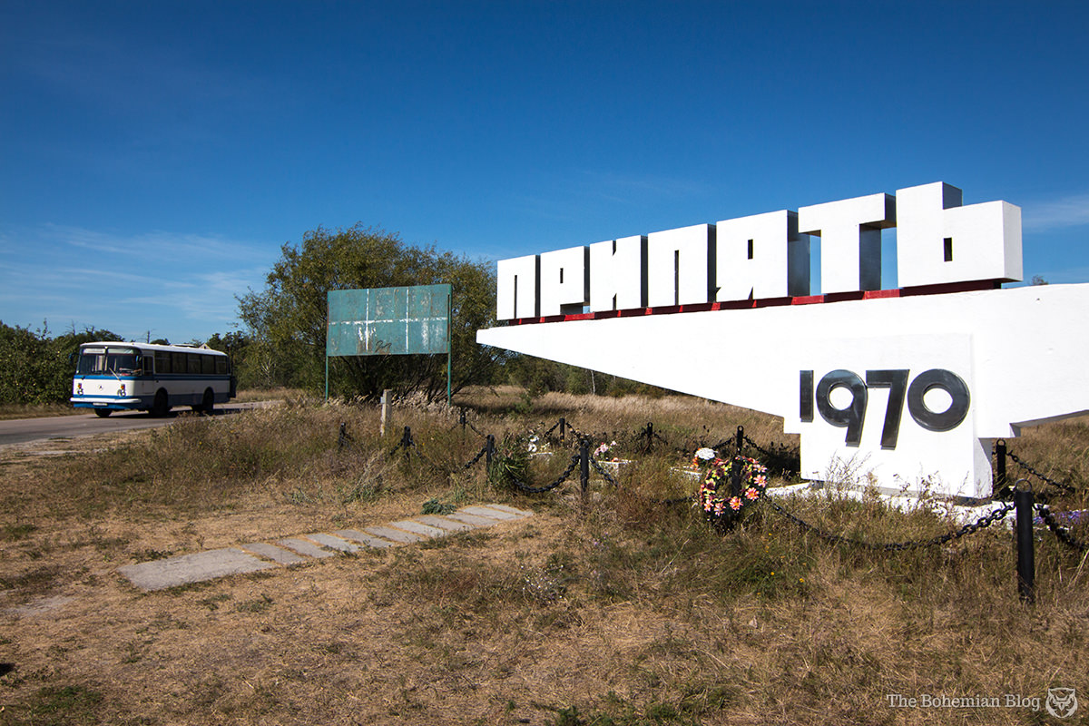 A tour bus passes the now iconic 'Pripyat' sign. Chernobyl Exclusion Zone, Ukraine.