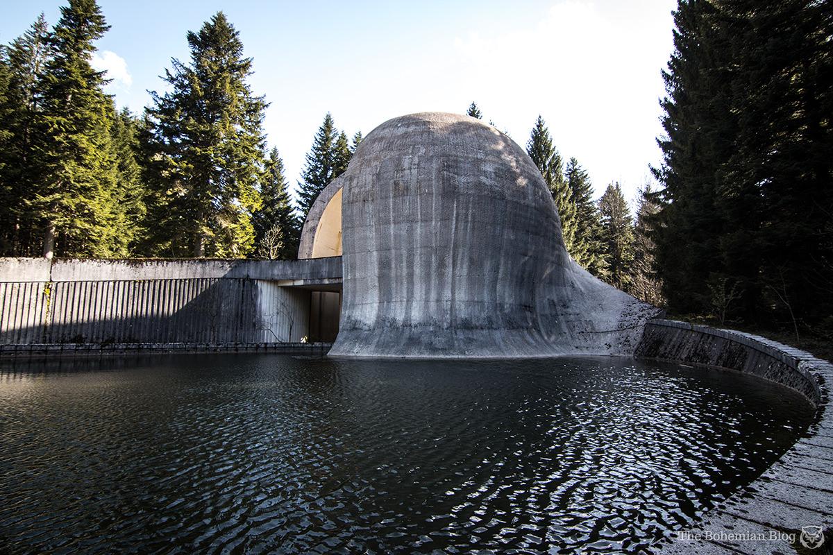 The Grmeč Monument rises above the stagnant memorial pool.