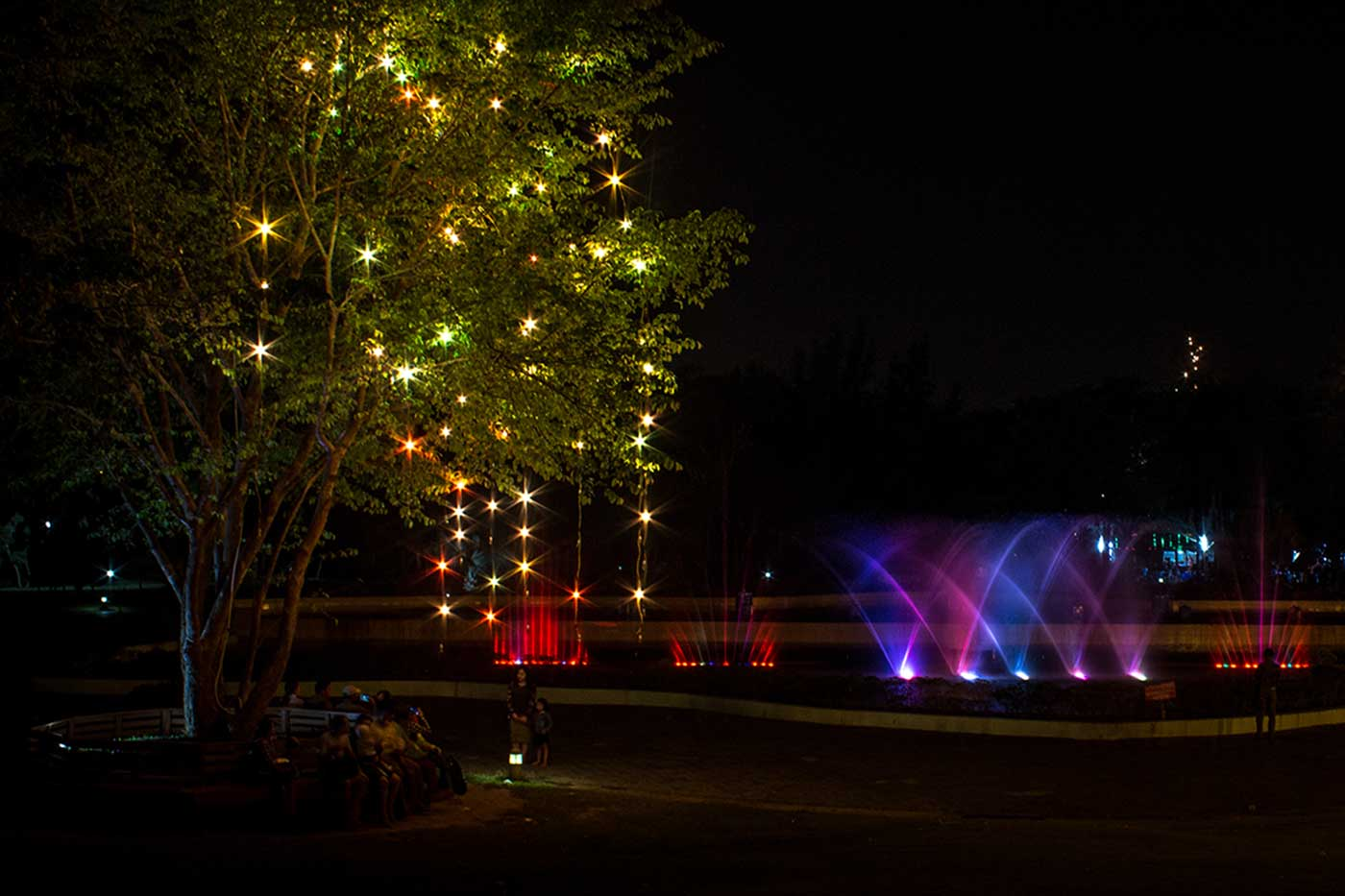 Locals relax in the Fountain Park after dark.