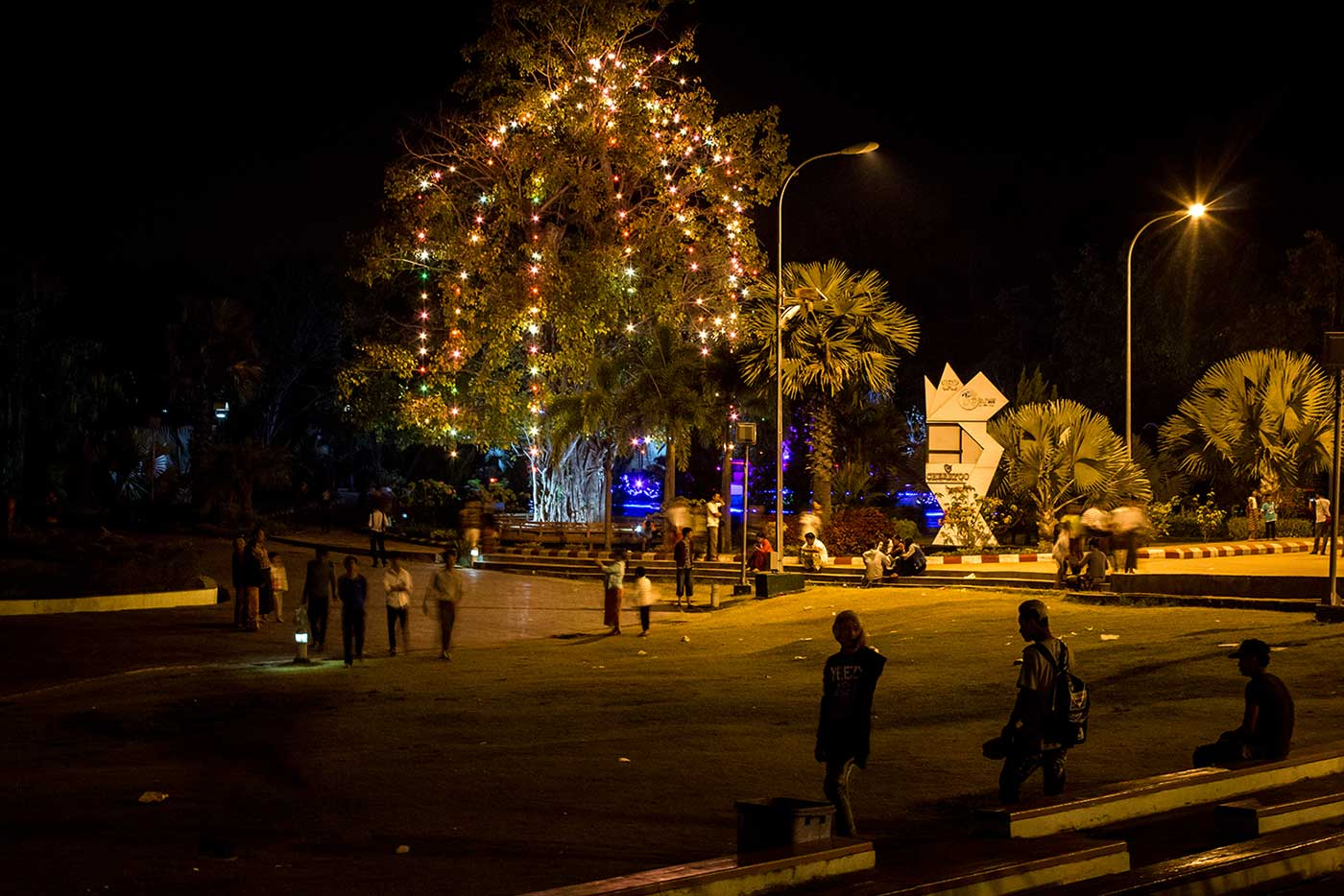 The Fountain Park is a popular evening hangout filled with people, music, and a festival atmosphere.