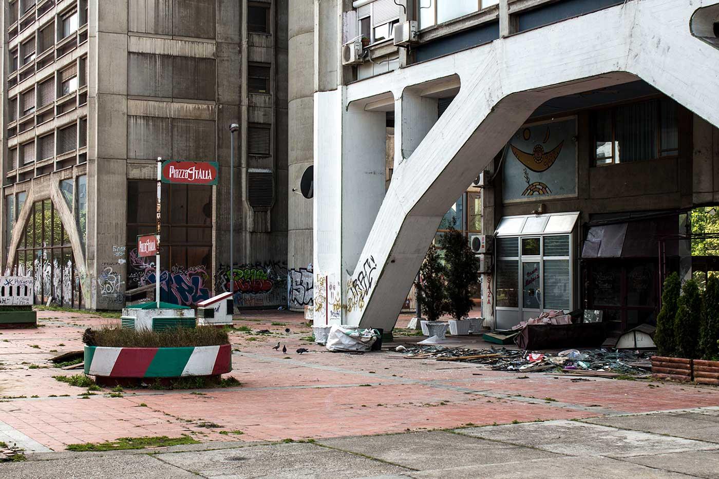 Broken tiles, litter and graffiti mar the plaza at ground level.