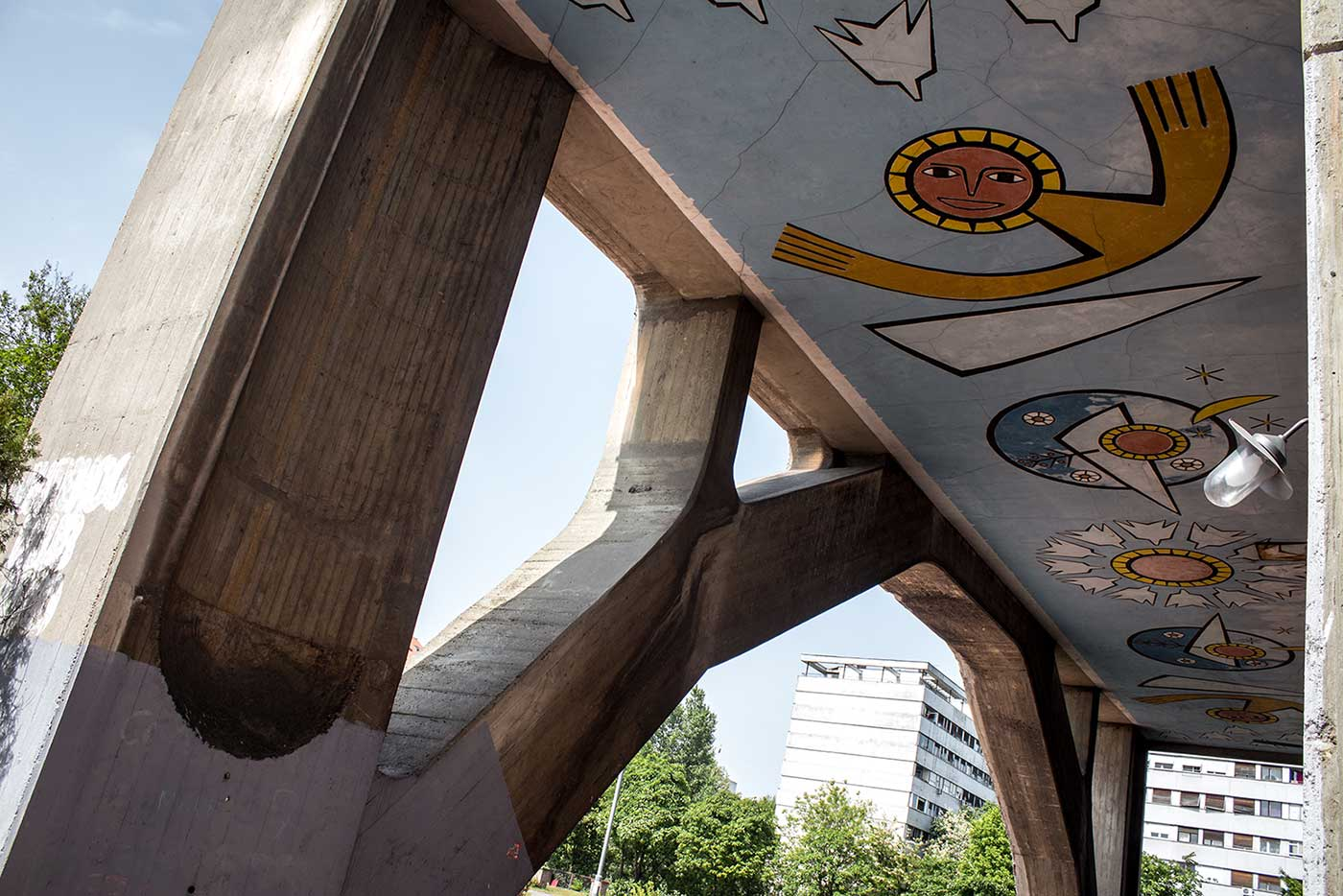 Brutalist colonnades circle the building at ground floor level – here, decorated with colourful Modernist murals.
