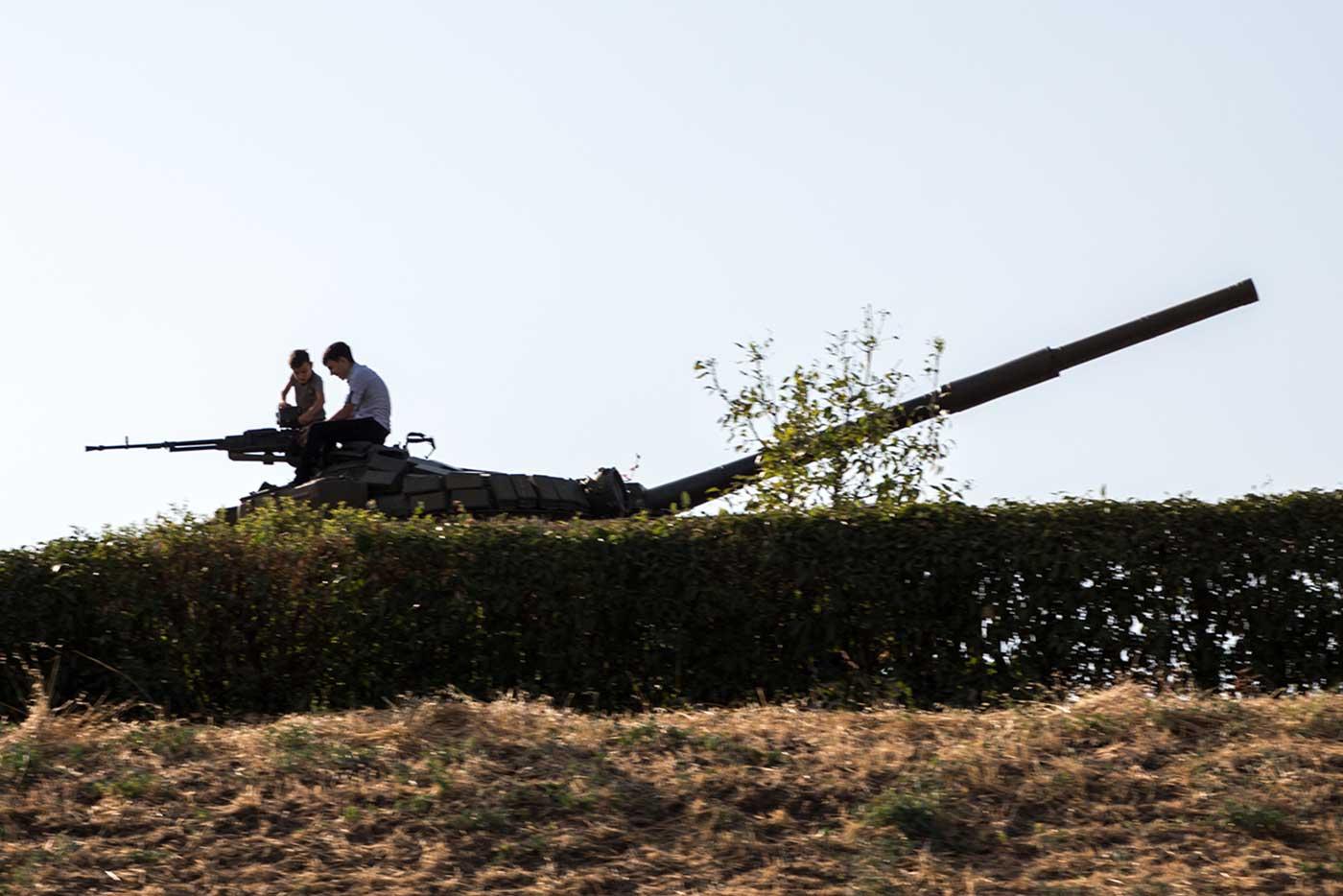 Young tourists play on a memorialised tank. Nagorno-Karabakh.