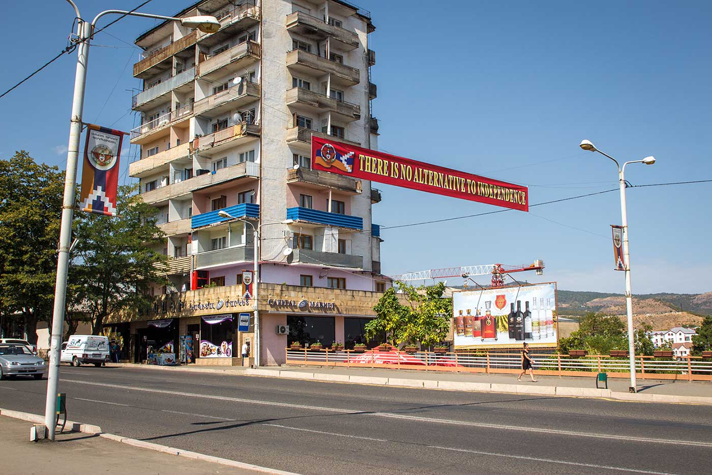 Flags and political banners fly above a billboard advertising wine and cognac. Stepanakert, Nagorno-Karabakh.