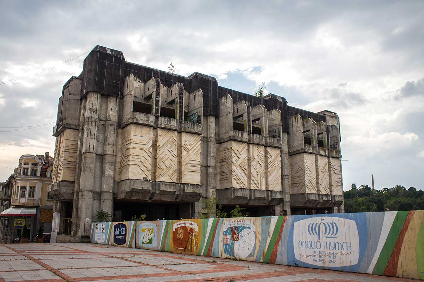 The six-storey western block of Shumen Central City Square rises behind a fence painted with vintage advertising. Bulgaria.