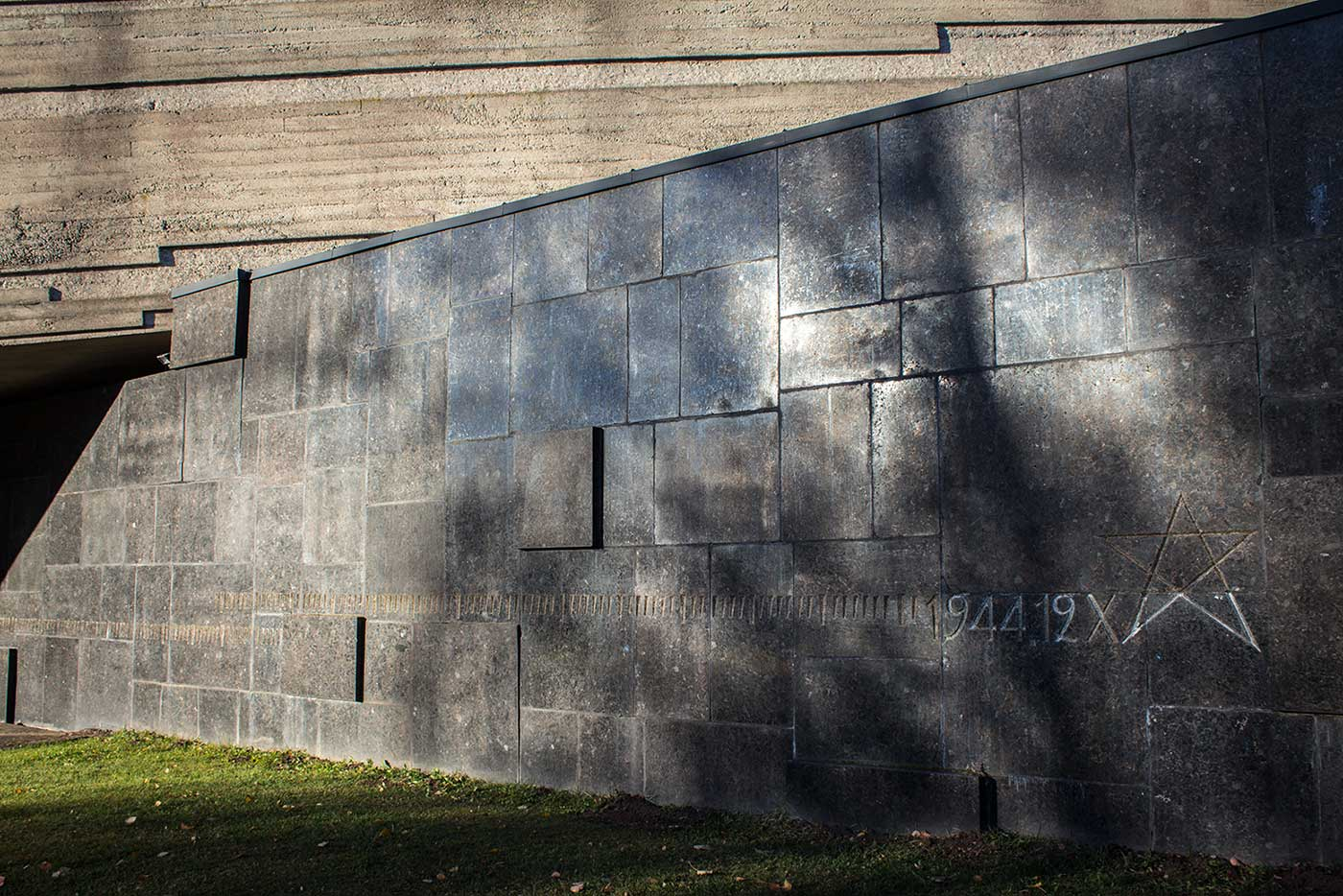 A symbolic tally etched into the new gallery building counts time inside the prison. Salaspils Memorial, Latvia.