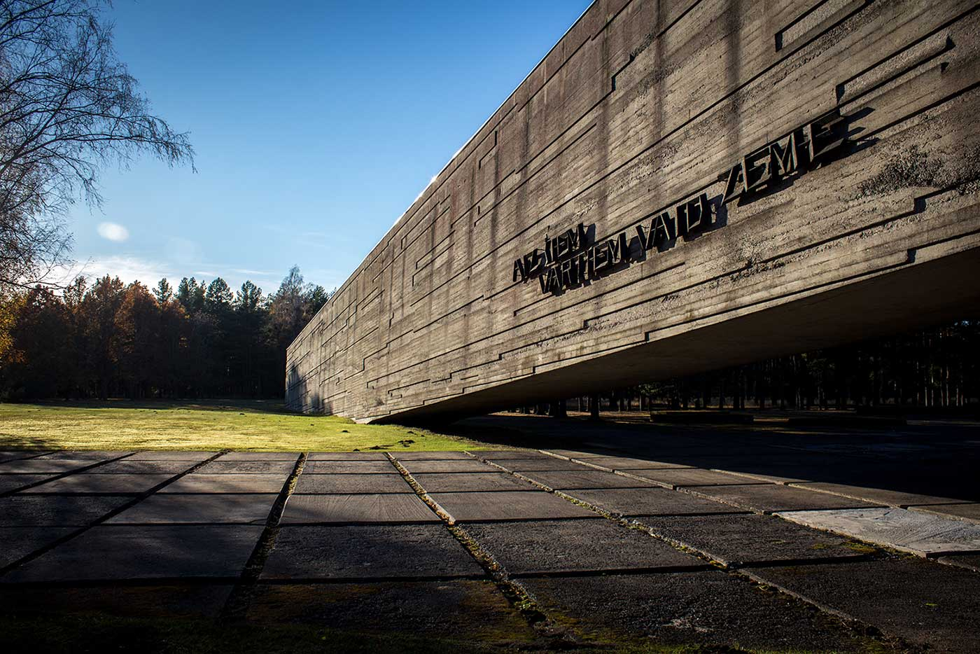 """Text across the wall of the gallery reads: """"Beyond these gates the land groans."""" Salaspils Memorial, Latvia."""