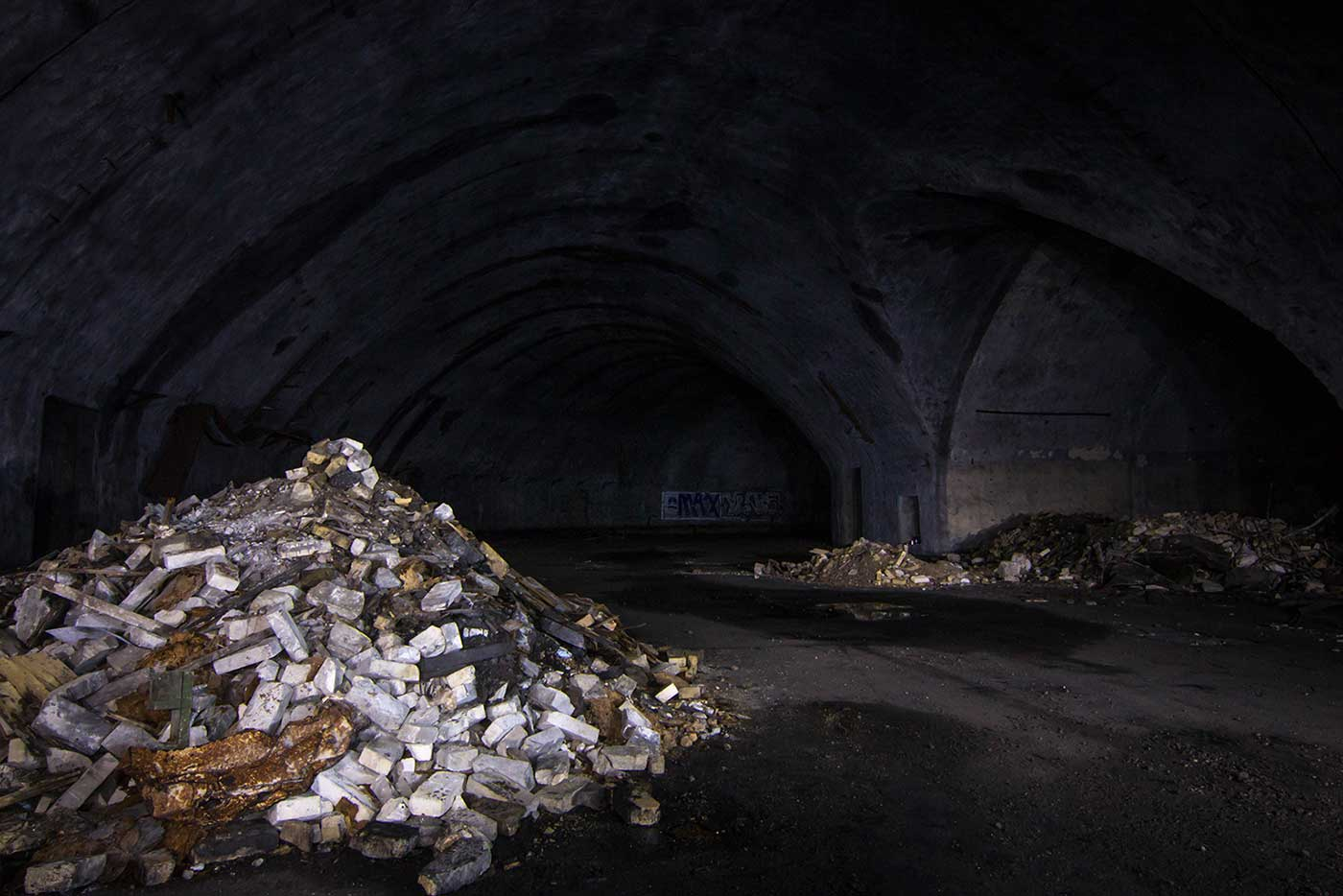 Today the underground aircraft galleries of the Željava Airbase are bare and abandoned, forming a pitch-black labyrinth beneath the mountain.