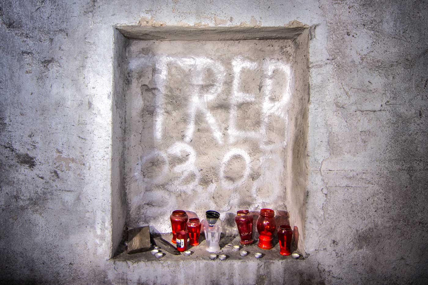 A memorial shrine set into a wall alcove deep within the 'KLEK' complex. Željava Airbase, Croatia.