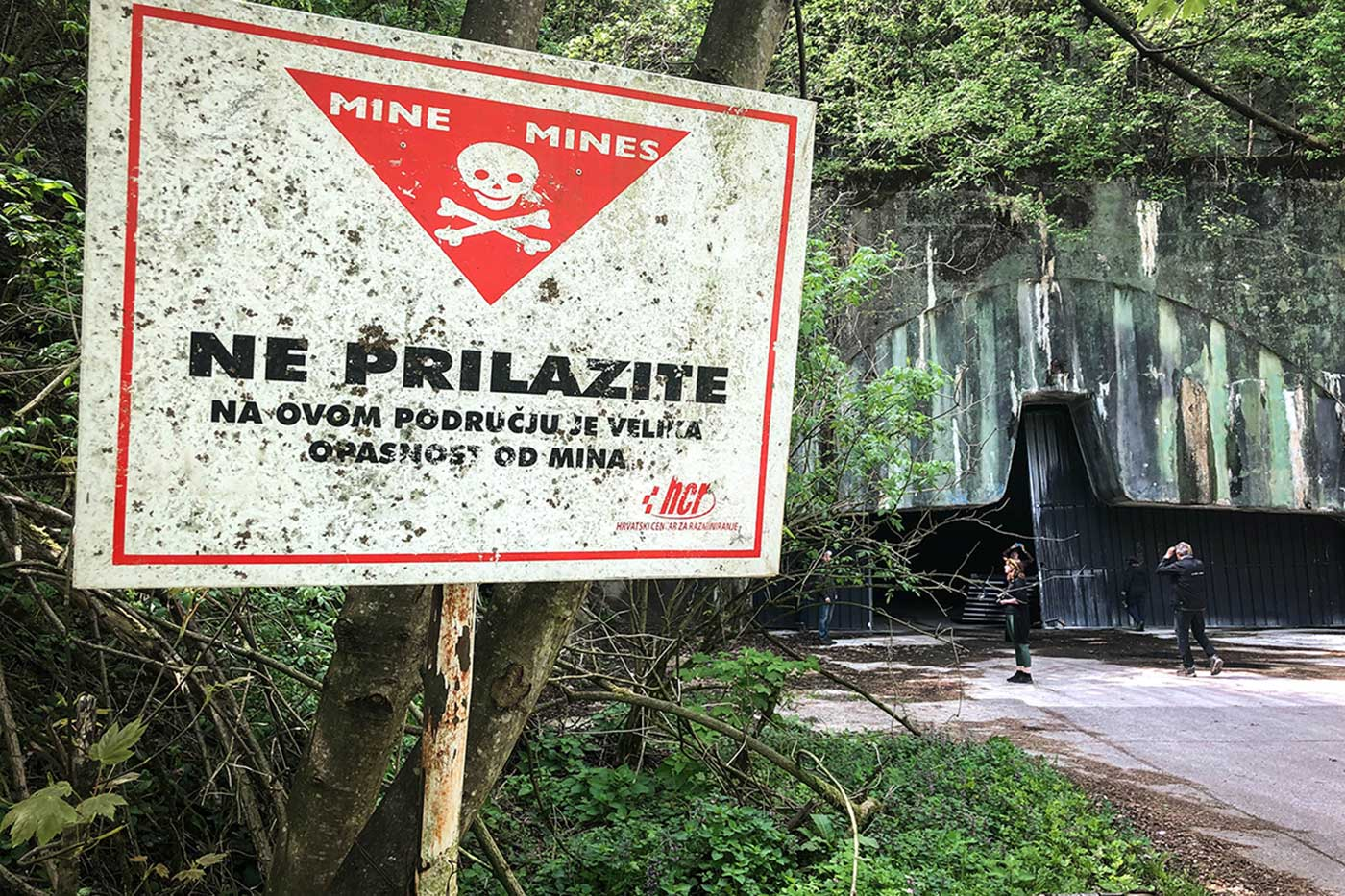 Signs around the entrance to the underground complex of Željava Airbase warn of unexploded landmines in the area.