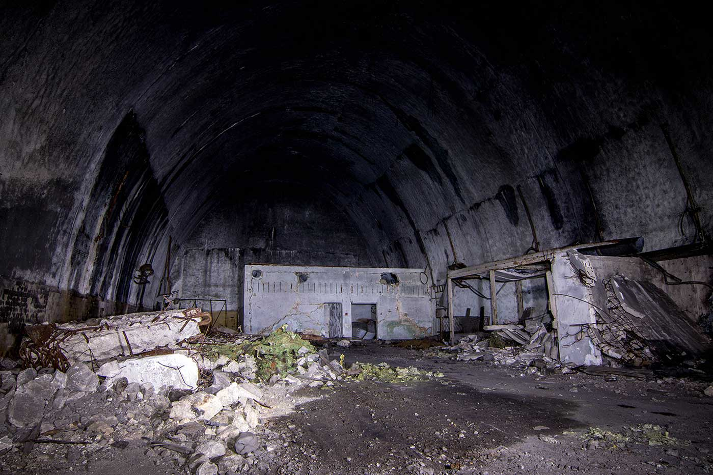The first chamber inside Entrance 2 of the 'KLEK' complex at Željava Airbase. The door frames set into the far block give an idea of scale.