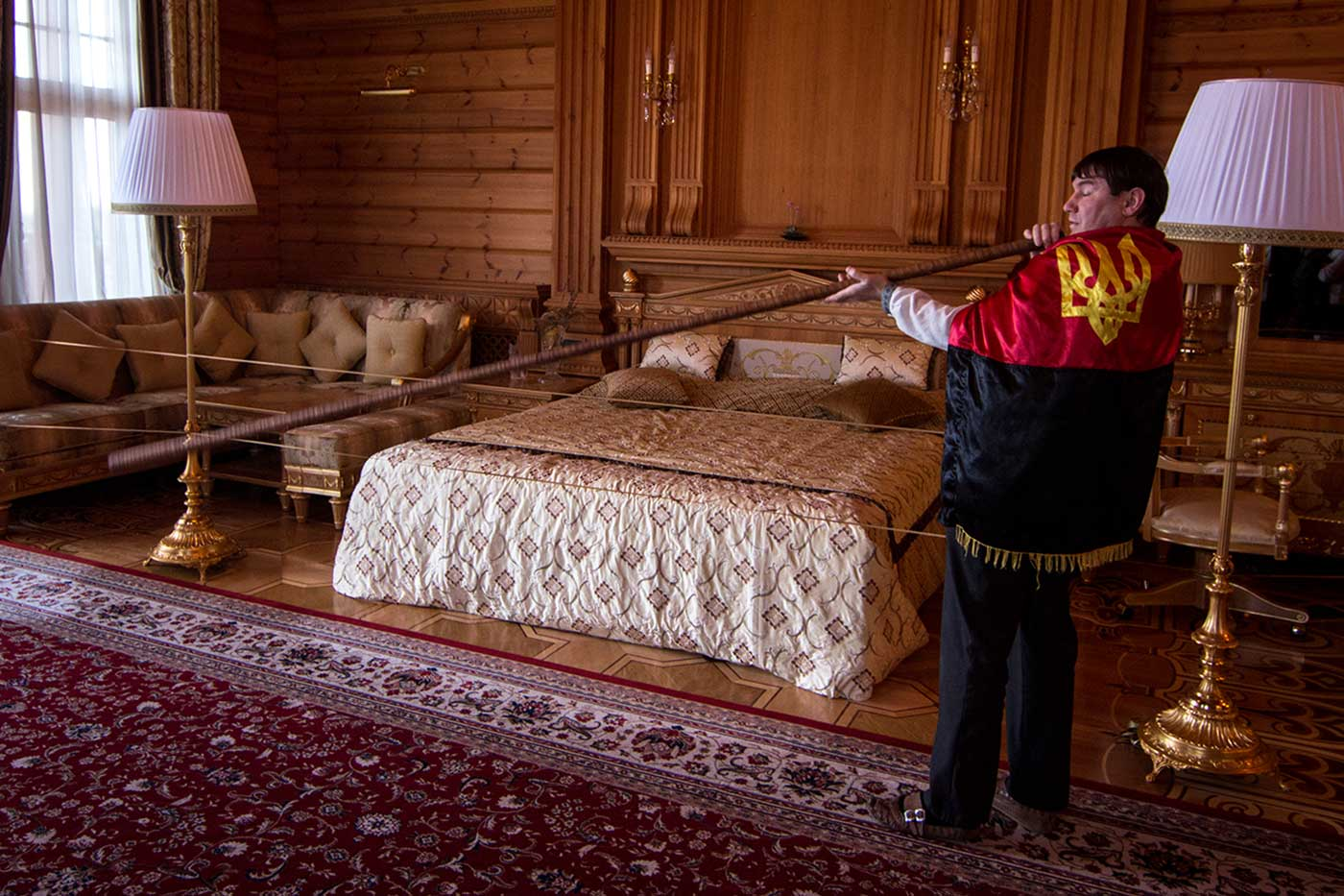 In Yanukovych's bedroom, Petro gives visitors a demonstration of the trembita – a traditional Ukrainian horn. Mezhyhirya, Ukraine.