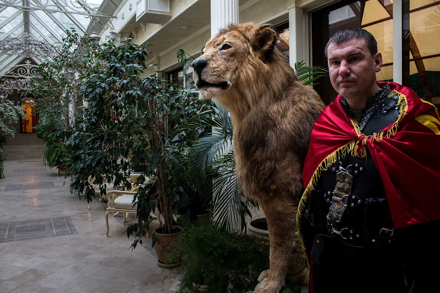 Petro Oliynik poses for a photograph beside a stuffed lion, in a corridor of Mezhyhirya's wellness complex.