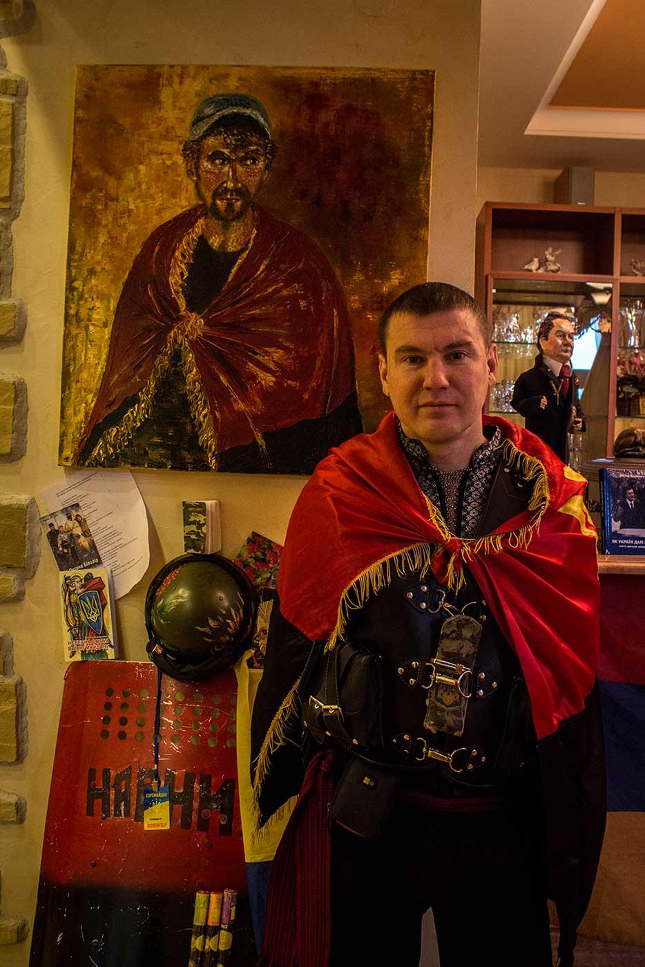 Petro Oliynik poses in front of a painting of himself. Mezhyhirya, Ukraine.