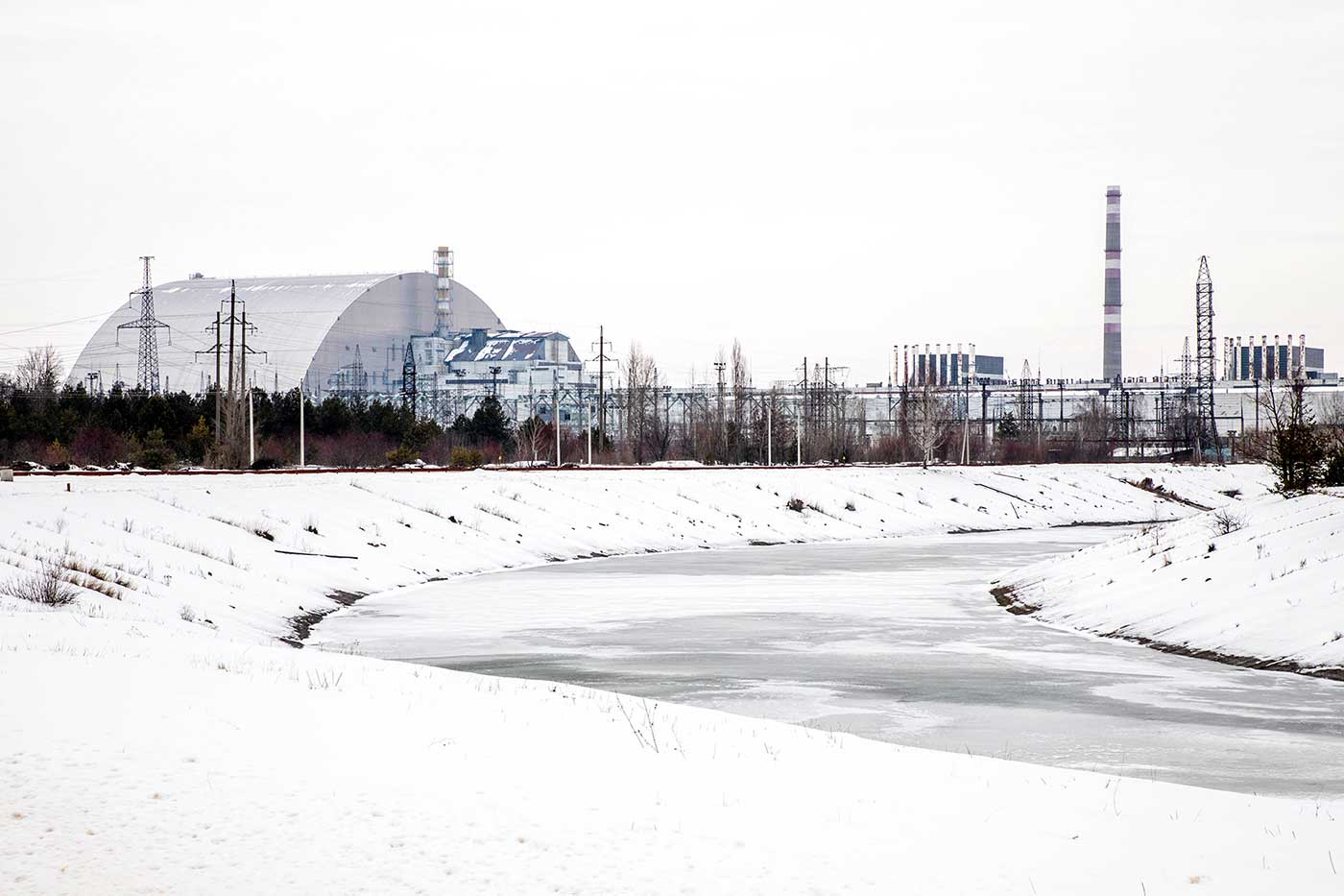 Chernobyl Nuclear Power Plant in winter. Visible from right to left are Reactor Blocks 1 and 2, the chimney and grey roof of Reactor Block 3, and finally, the New Safe Confinement structure encasing the destroyed Reactor Block 4.