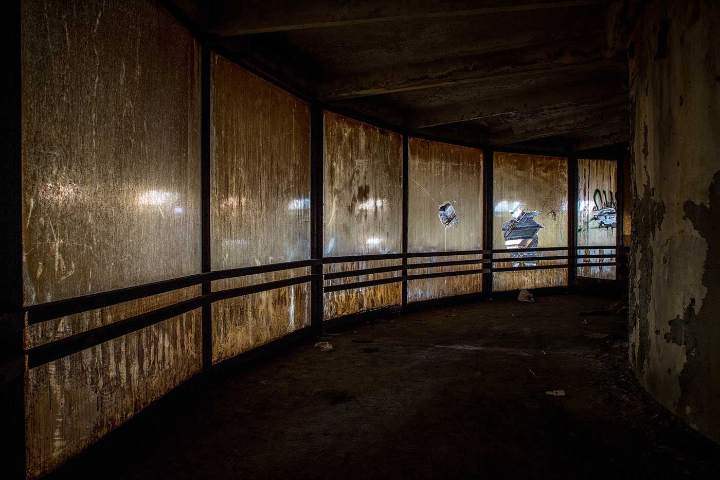 The glass windows of the panopticon-style platform at the top of the central pillar are discoloured by years' worth of accumulated dust and dirt. Autobus Park №7: the abandoned bus depot in Kyiv, Ukraine.