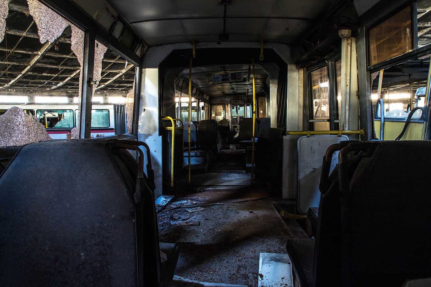 Inside the remains of an articulated urban bus. Autobus Park №7: the abandoned bus depot in Kyiv, Ukraine.