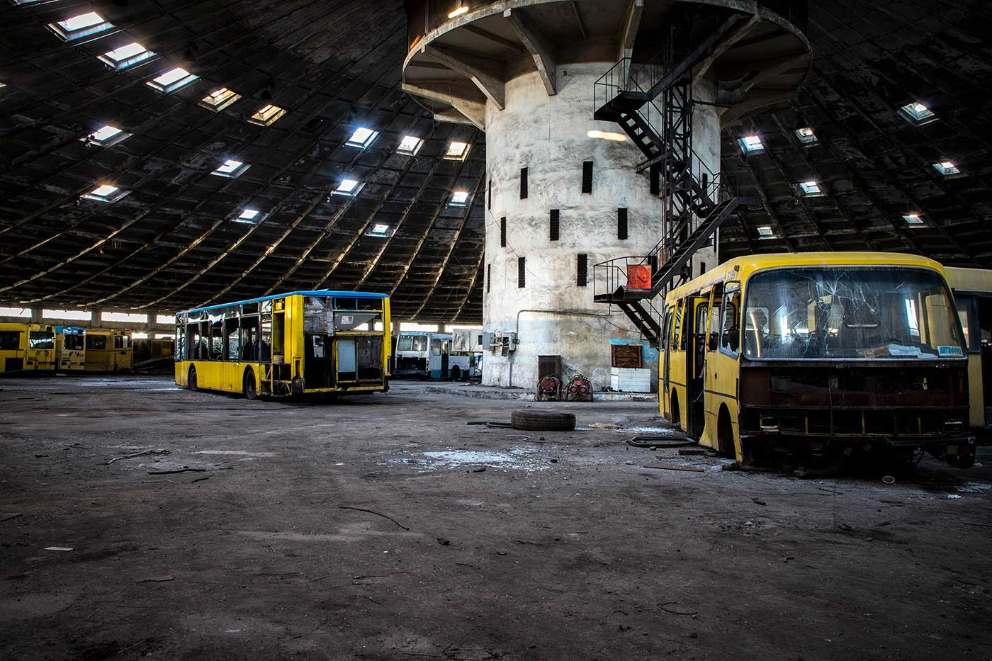 Attached to the 18m central support pillar, a metal staircase leads up to an observation platform. Autobus Park №7: the abandoned bus depot in Kyiv, Ukraine.