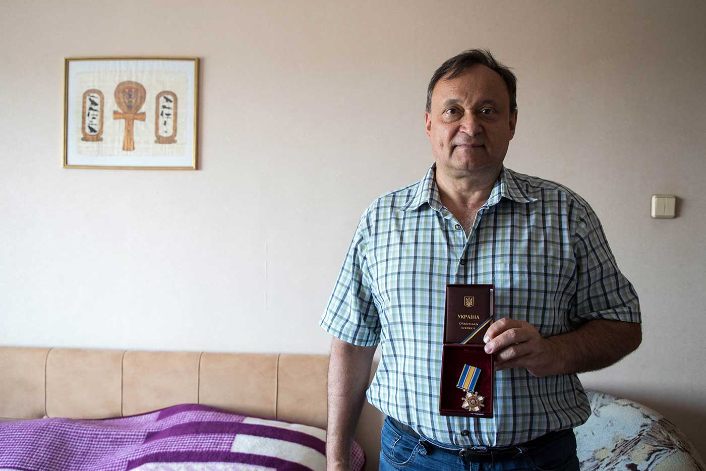Alexei Ananenko at home in September 2019, holding the Order of Courage medal awarded to him the previous year by President Petro Poroshenko.